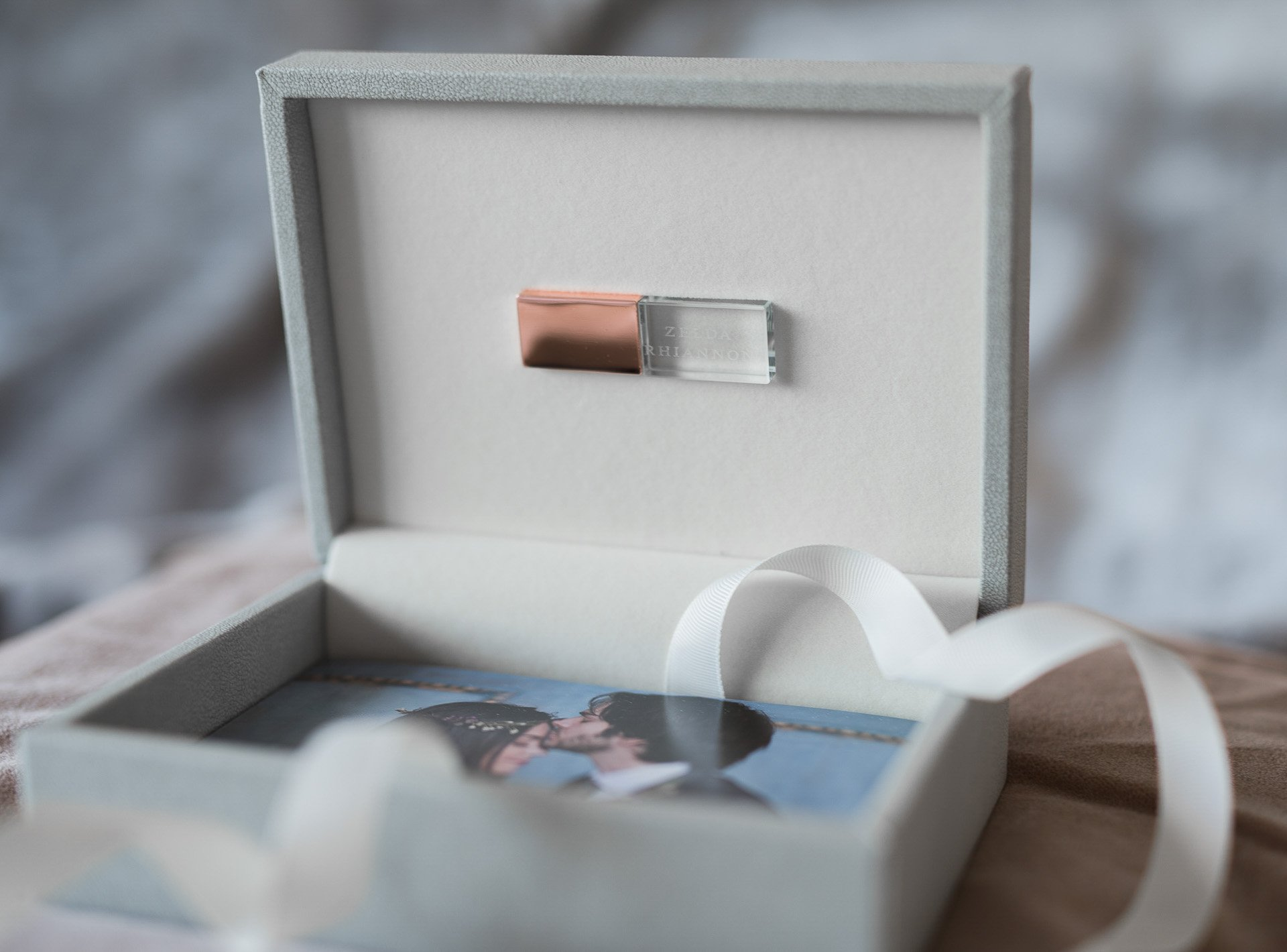 a grey usb box with rose gold usb inside and some photos