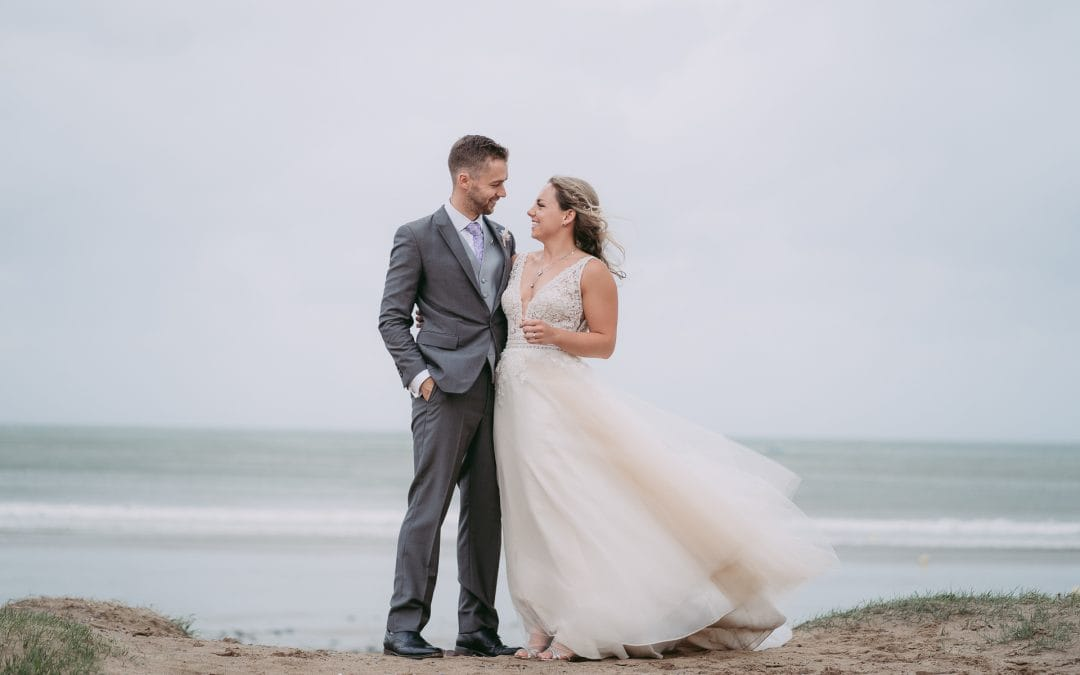 bride and groom standing on a beach smiling at each other