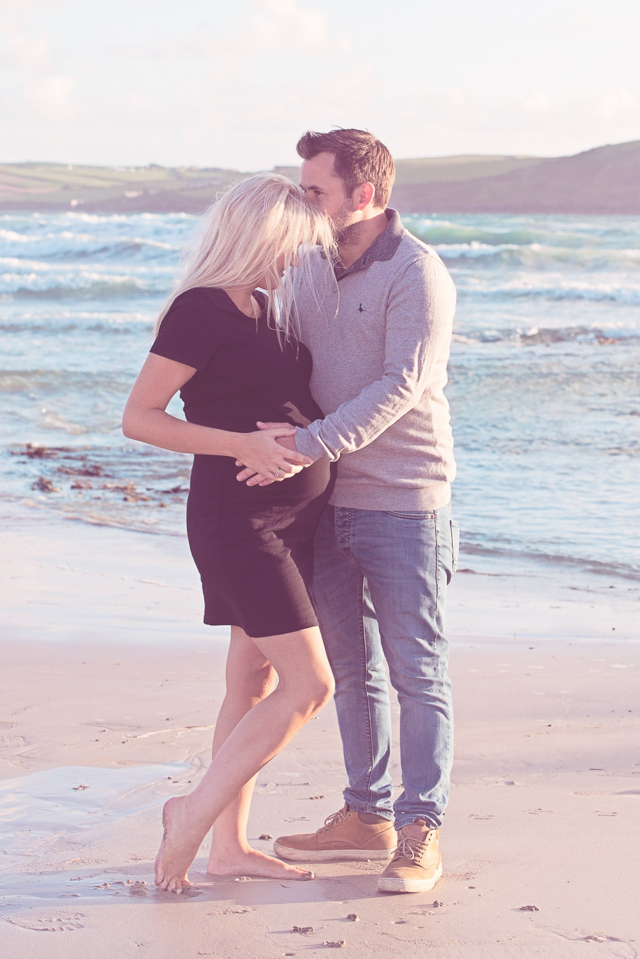 a couple on a beach during a maternity photography shoot