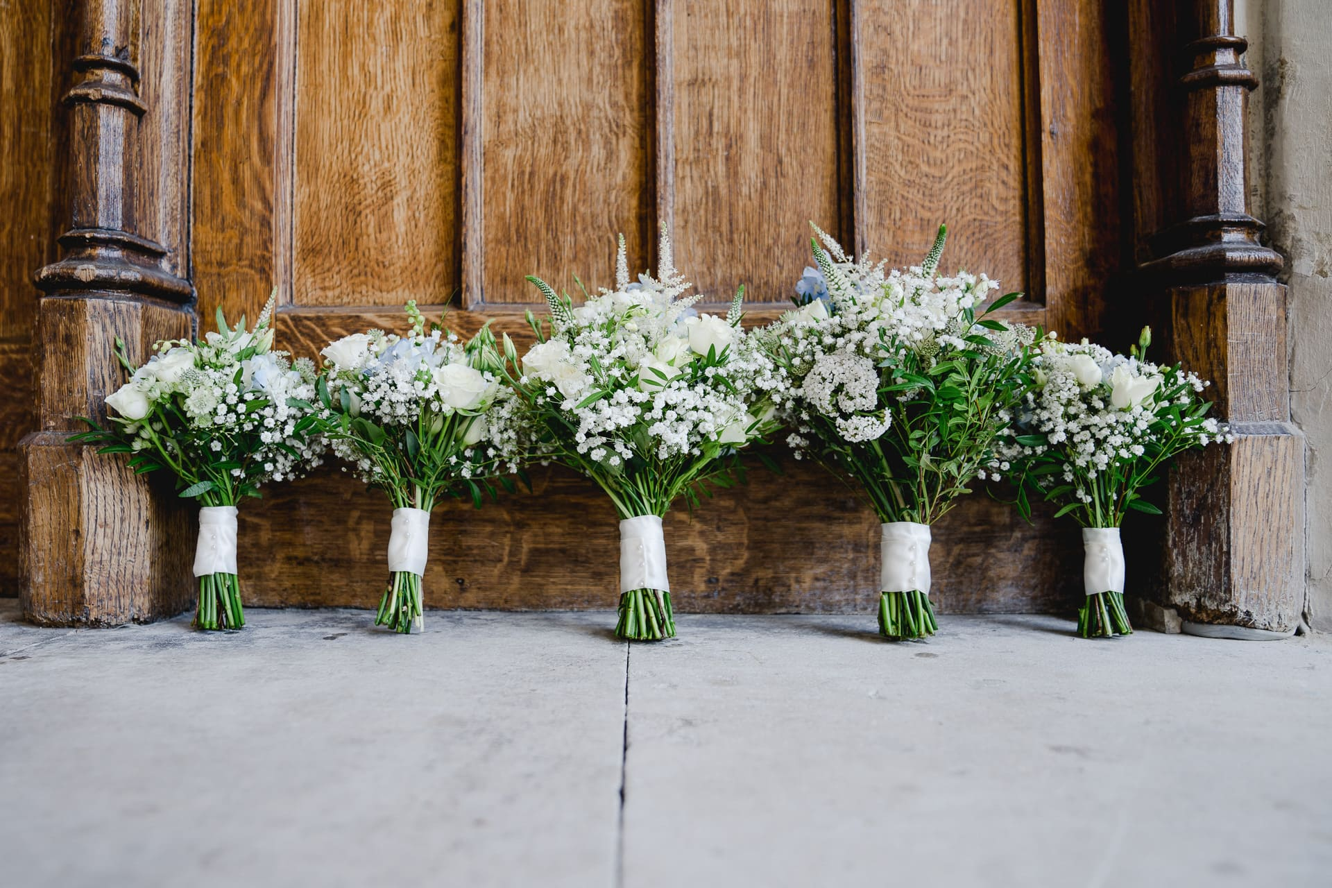 fine art wedding photography image of five bouquets of flowers in front of a wooden door