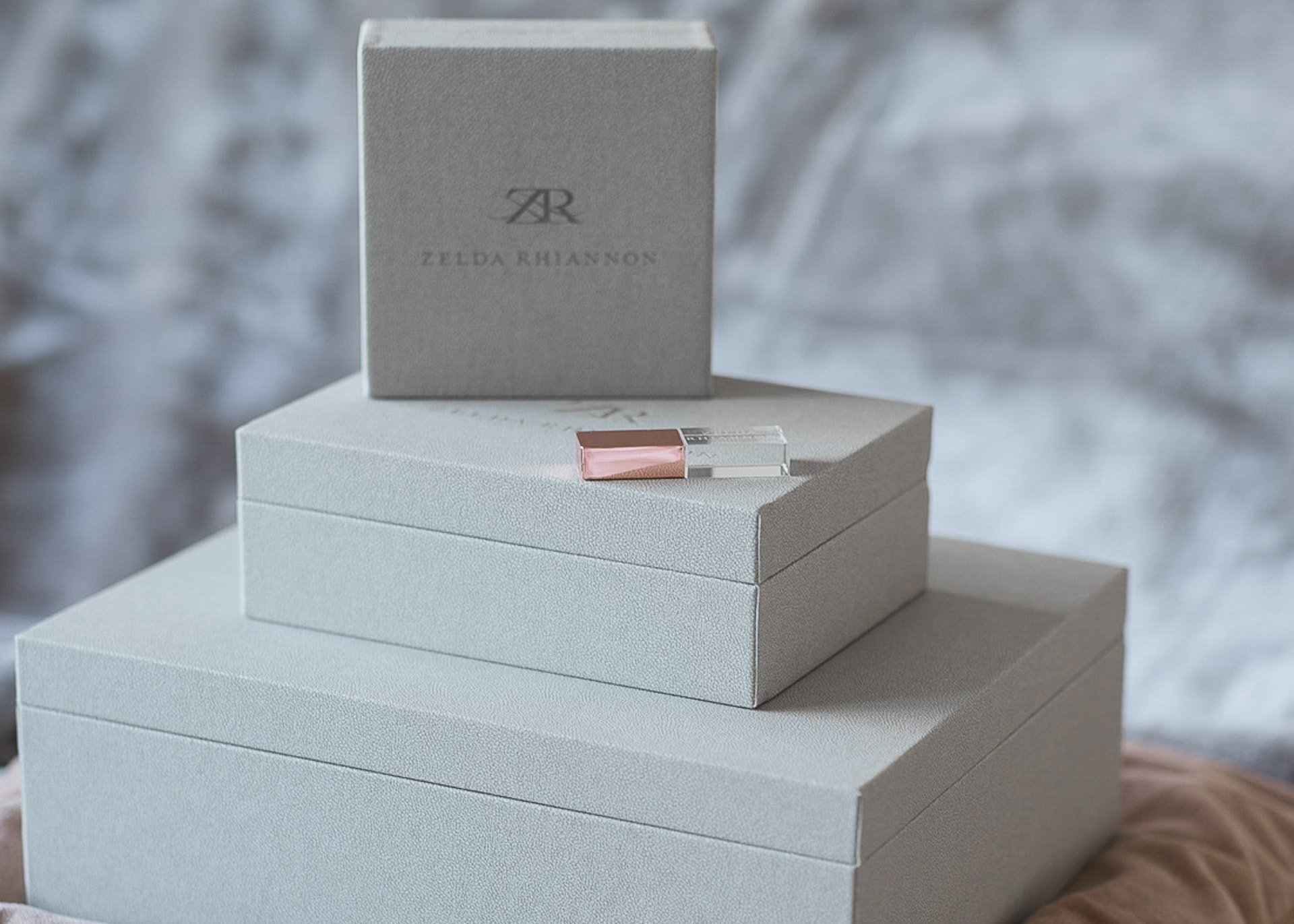 a usb with a rose gold lid on top of three grey boxes