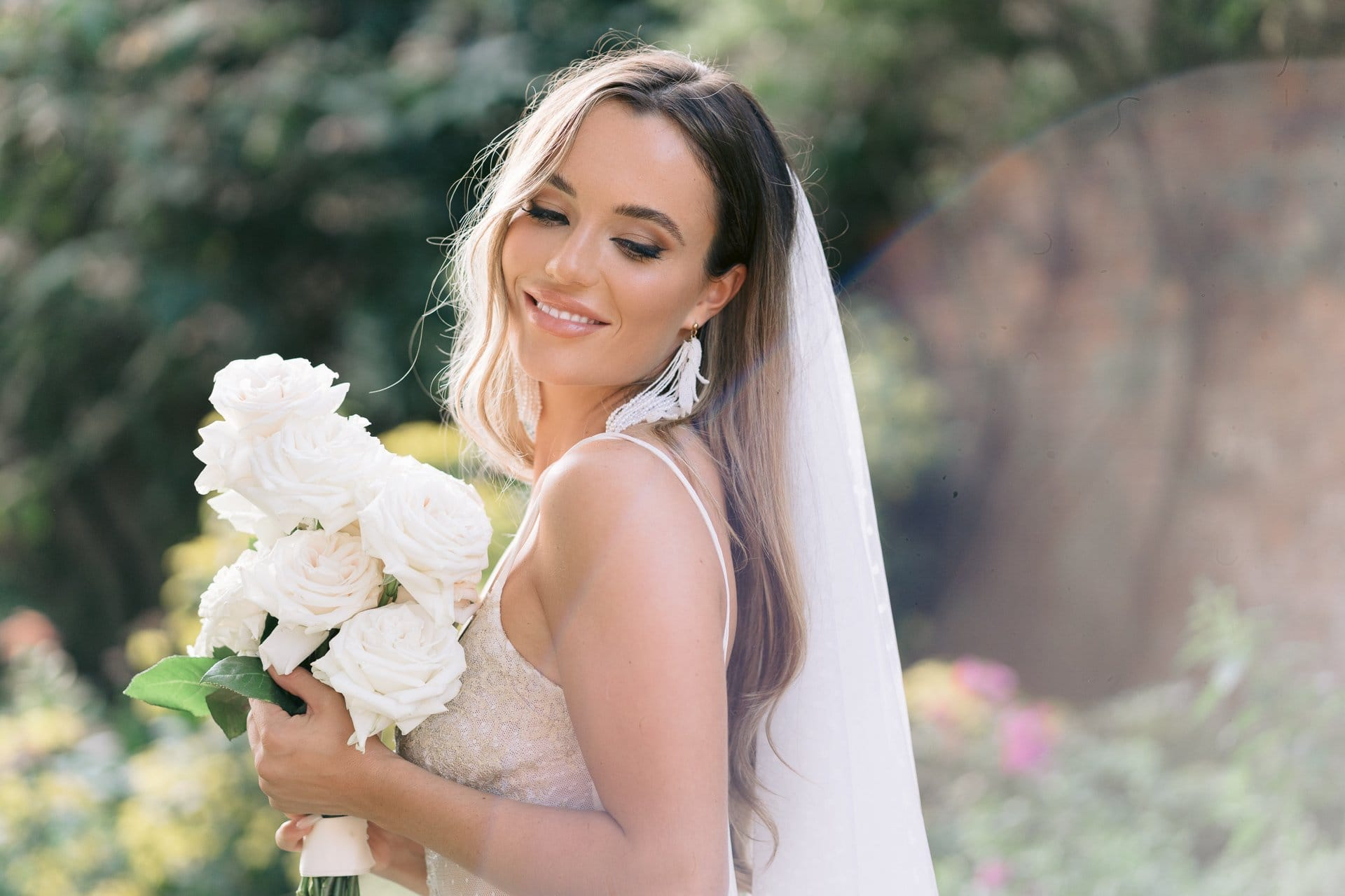portrait of a bride holding a white bouquet outside in the sunlight