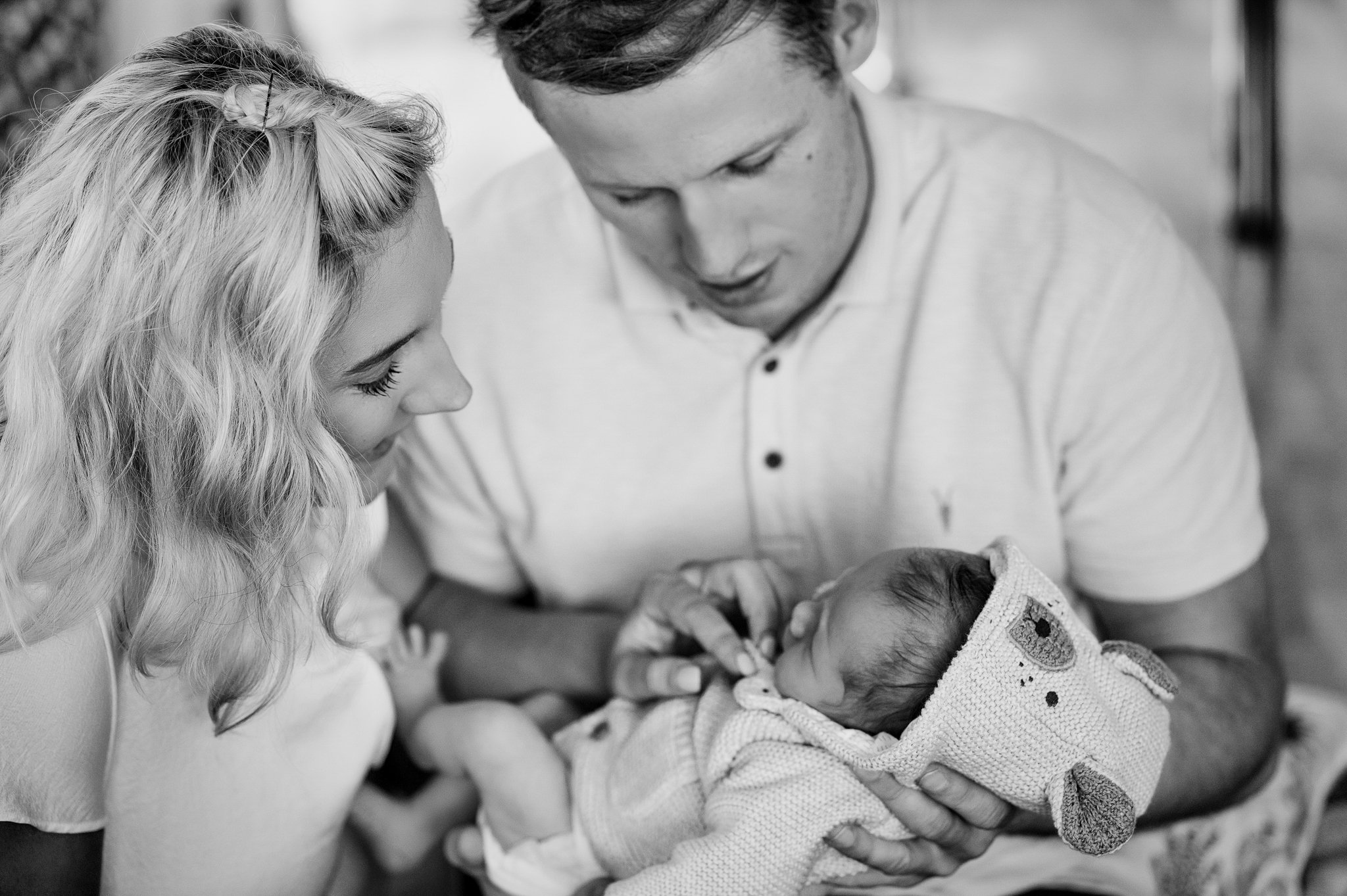 black and white image of a young couple holding a new baby