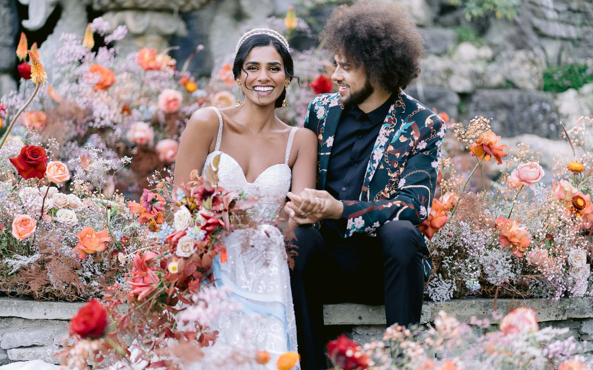 bride and groom sitting amongst lots of bright flowers smiling